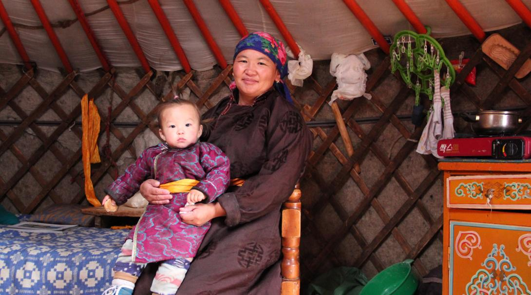 A Mongolian nomad woman and child sit in their ger